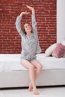 目を覚ます後腕を伸ばして女性