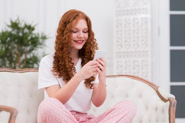 Молодая женщина на диване с помощью мобильного телефона