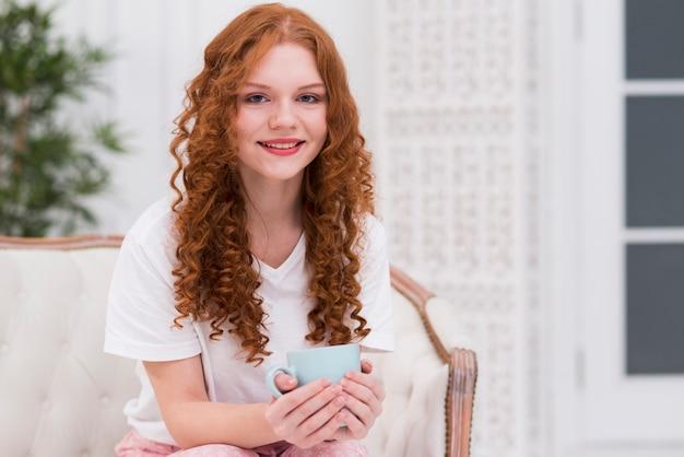Улыбающаяся женщина с рыжими волосами пьет чай