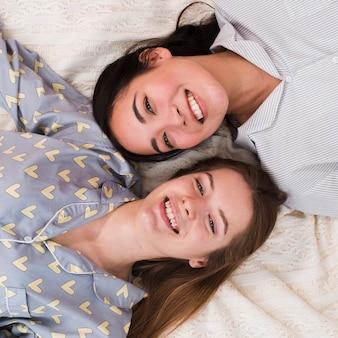 Улыбающиеся подружки сидят лежа в постели