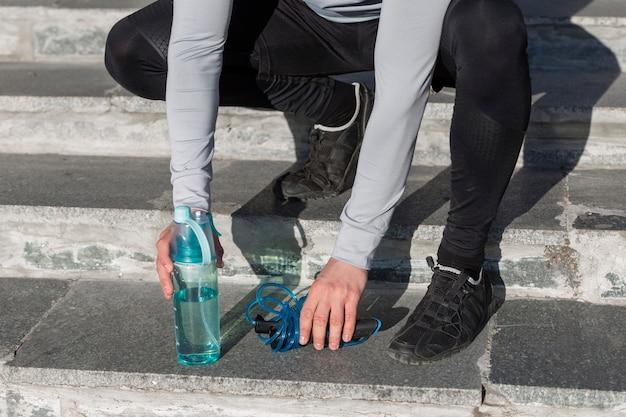 Мужские руки хватая бутылку воды и прыгая через скакалку