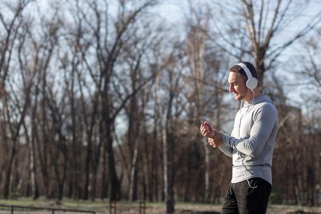 Атлетик человек прослушивания музыки в лесу с копией пространства