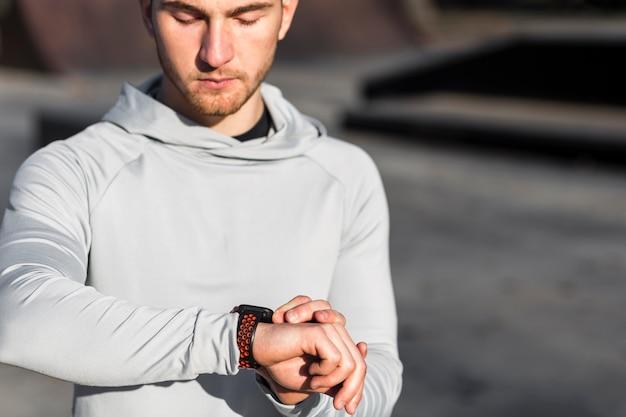 彼のスポーツの腕時計を調整するフロントビュー男