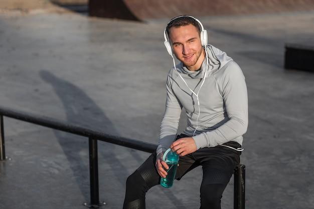 Спортивный человек слушает музыку и держит бутылку воды