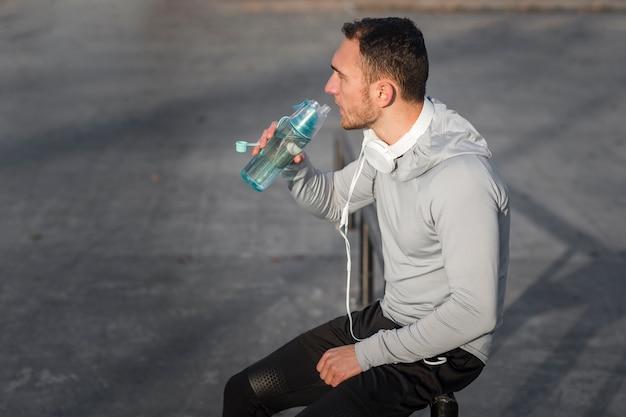 スポーティな若い男は、水を飲む