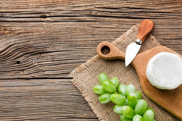 カマンベールフラットとコピースペースを持つ木製のまな板の上のブドウを置く