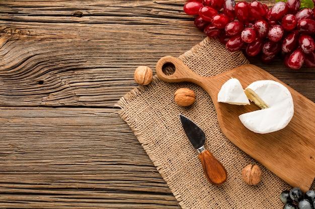Плоские кладут виноград и грецкие орехи камамбер на деревянной разделочной доске с копией пространства