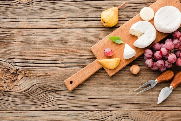 Вид сверху микс гурманов на деревянной разделочной доске винограда и посуды с копией пространства