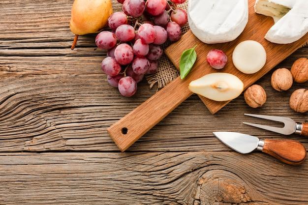 Вид сверху ассортимент изысканного сыра на деревянной разделочной доске с виноградом и посудой