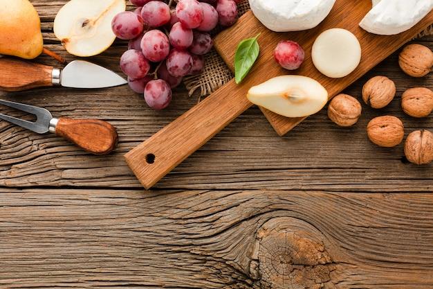 Вид сверху ассортимент изысканного сыра на деревянной разделочной доске с виноградными грецкими орехами и посудой