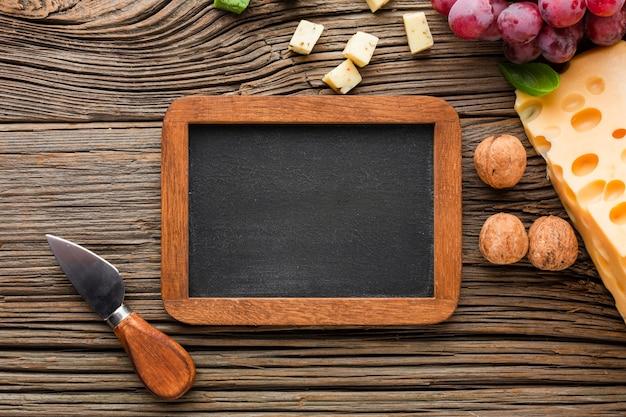 フラットレイアウトチーズブドウクルミと空白の黒板