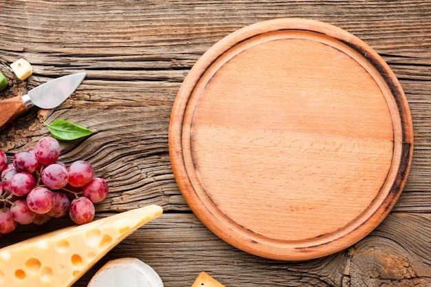 木製のまな板とフラットレイアウトブドウエメンタールとチーズナイフ
