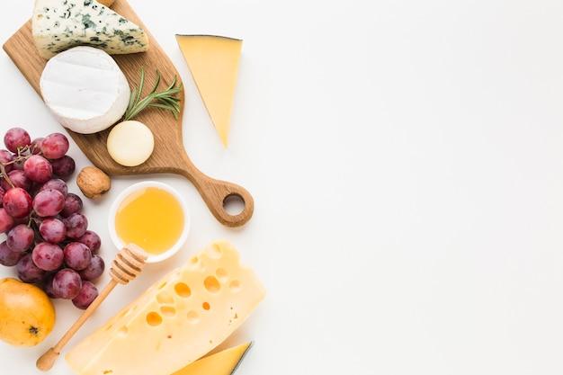 Вид сверху изысканный ассортимент сыра на деревянной разделочной доске и виноград с копией пространства