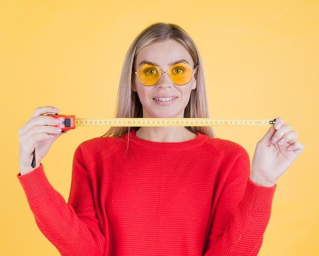Вид спереди женщина, держащая измерительная лента