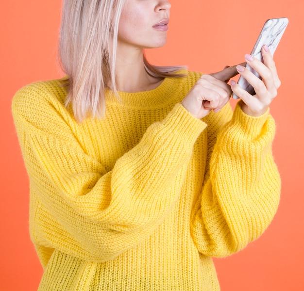 電話のスタジオショットをクリックする女性