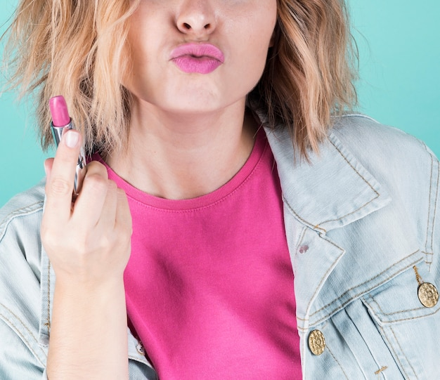 ピンクの口紅を保持しているガーリーなモデル