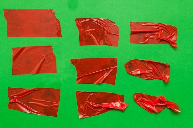Части красной ленты на зеленой стене