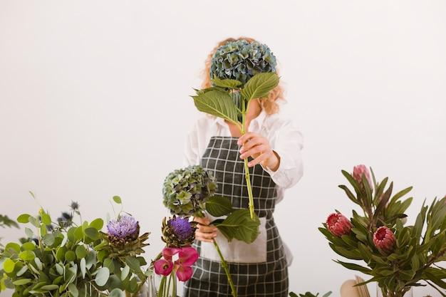 Среднего роста флорист закрывает лицо букетом