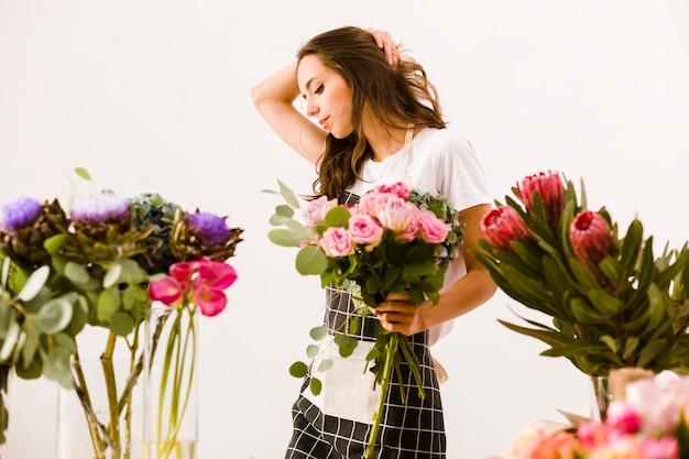 Флорист среднего размера позирует с букетом в помещении