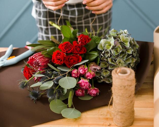Флорист крупным планом, используя нить для букета