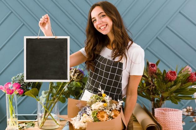 Средний снимок счастливый флорист держит черную доску
