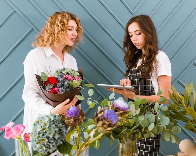 花束とタブレットを持つミディアムショット女性