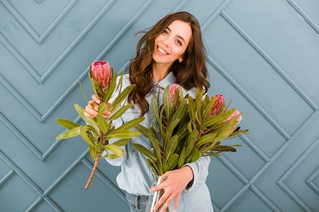 正面の幸せな女性が花でポーズ