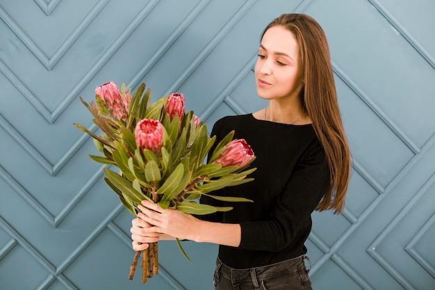 ミディアムショットの若い女性が花でポーズ