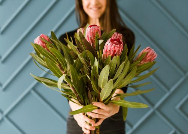 花束を保持しているクローズアップスマイリー若い女性