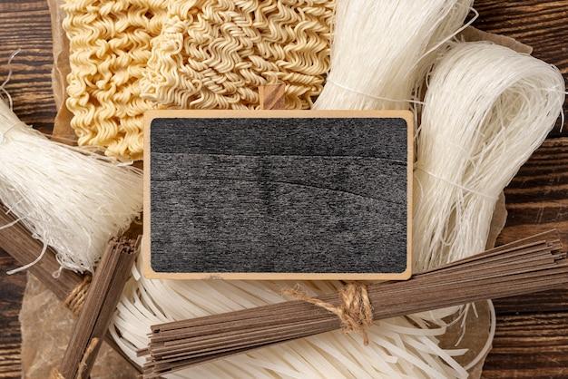 空の黒板と木製の背景に麺の未調理の品揃えを置く