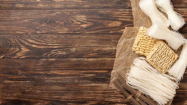 コピースペースを持つ木製の背景に麺のフラットレイアウト未調理
