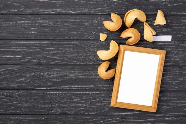 コピースペースと空白のフレームを持つフラットレイアウトフォーチュンクッキー