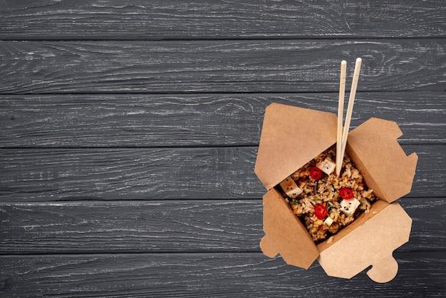 Плоский рис и овощи на вынос и палочки для еды с копией пространства