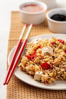Рис с высоким углом с овощами, соевым соусом и палочками