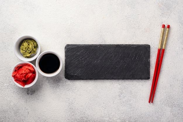 Плоские лежал имбирь васаби соевый соус миски и палочки для еды