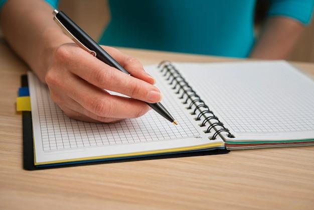 Вскользь женщина пишет в тетради в клетку