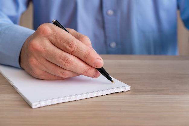 До неузнаваемости деловой человек пишет в блокноте