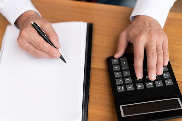 Вид сверху корпоративного человека с помощью калькулятора