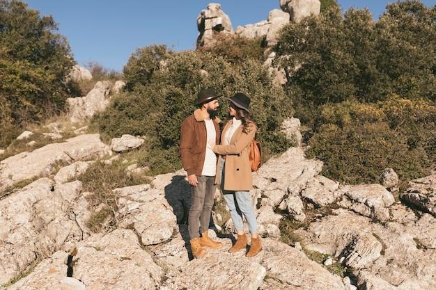 山の風景でポーズをとる若いカップル