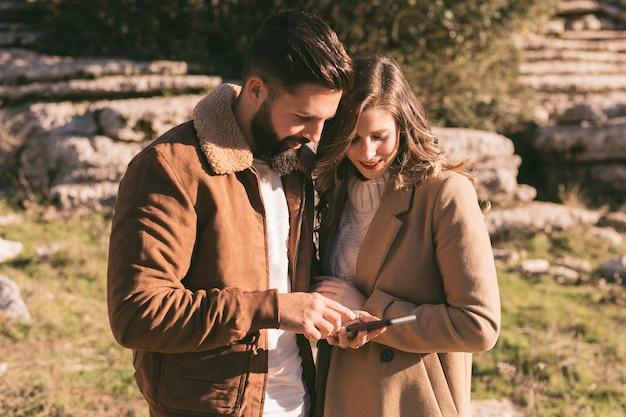 Молодая пара смотрит на телефон