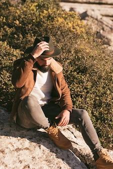 Красивый мужчина позирует моды на природе