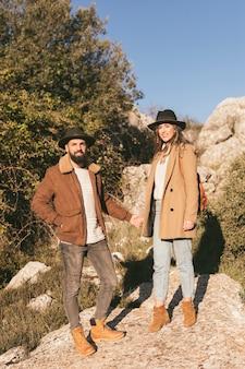 Молодая пара, держась за руки и глядя на фотографа