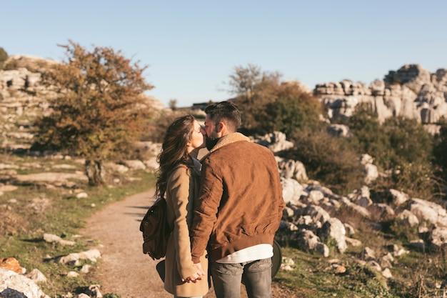 自然の中でキスする美しいカップル