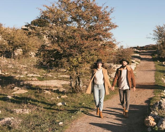 フロントビューの男性と女性が一緒に歩いて