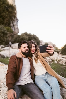 Улыбающаяся пара, делающая селфи на скале