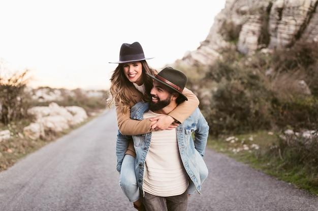 Мужчина держит красивую женщину и идет по дороге