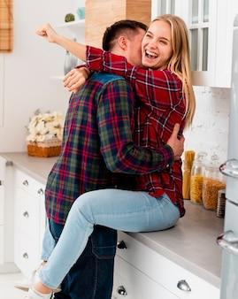 Средний снимок парень целует девушку на кухне