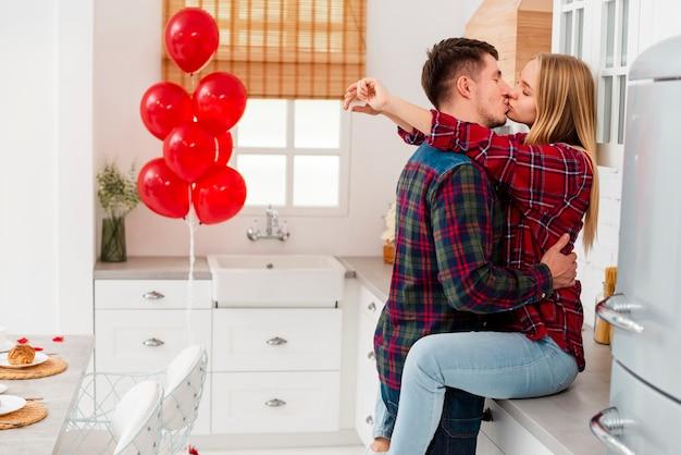 ミディアムショットのカップルが台所でキス