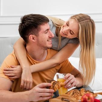 ベッドでの朝食とミディアムショットカップル