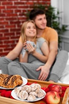 ベッドでの朝食とミディアムショットぼやけカップル